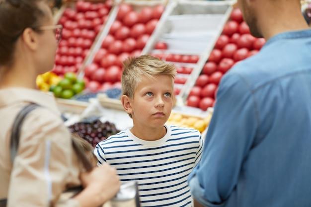 Junge, die mit eltern im supermarkt einkauft