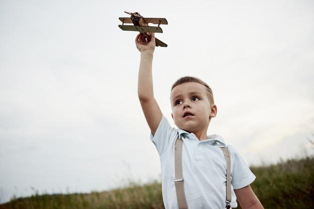 Junge, die mit seinem spielzeug-holzflugzeug auf dem feld voll des hohen grases spielt.
