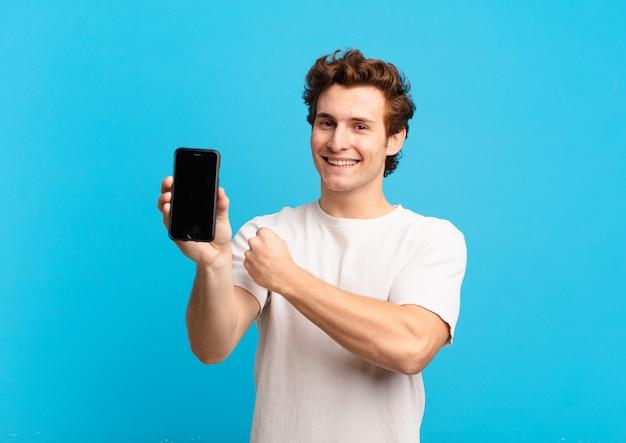 Junge, die sich glücklich, positiv und erfolgreich fühlen, motiviert sind, wenn sie sich einer herausforderung stellen oder gute ergebnisse feiern. telefonbildschirmkonzept
