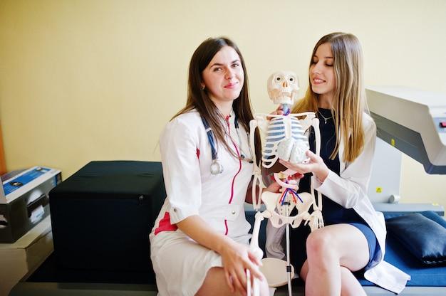Junge doktoren, die spaß haben, indem sie mit dem skelett aufwerfen.