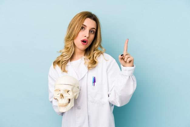 Junge doktorfrau, die einen schädel isoliert hält, der eine große idee, konzept der kreativität hat.