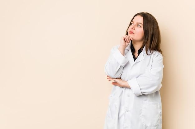 Junge doktorfrau, die seitlich mit zweifelhaftem und skeptischem ausdruck schaut.