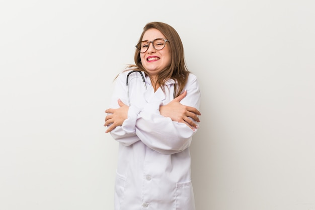 Junge doktorfrau gegen eine weiße wand, die wegen der niedrigen temperatur oder einer krankheit kalt geht
