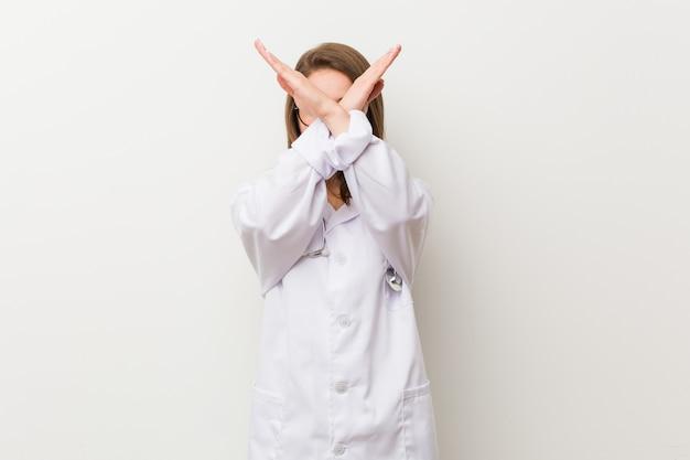 Junge doktorfrau gegen eine weiße wand, die zwei arme gekreuzt, ablehnungskonzept hält.