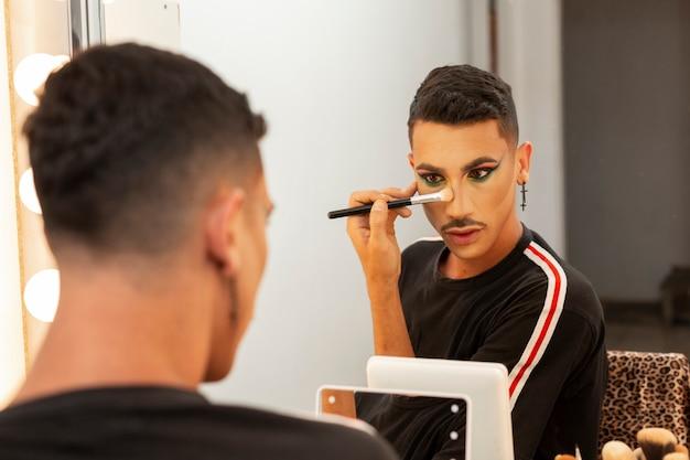 Junge drag-queen-künstlerin schminkt sich in der umkleidekabine