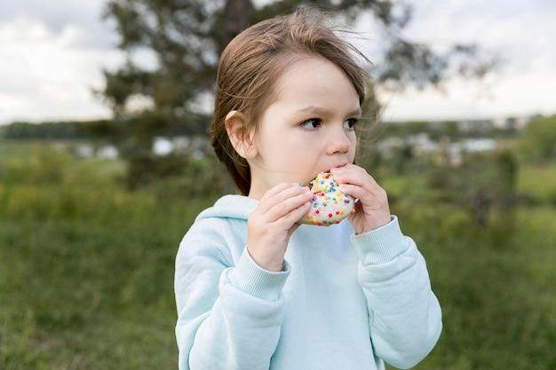 Junge draußen essen einen donut
