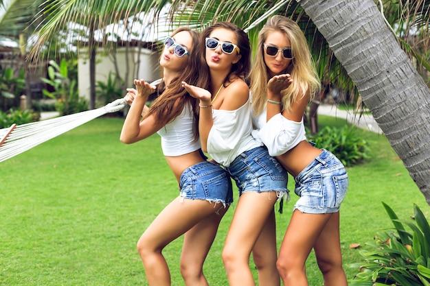 Junge drei glückliche schöne mädchen, die spaß an der sommerzeit haben und im park posieren