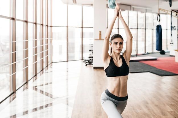 Junge dünne attraktive frau mit übendem yoga des langen haares zuhause.