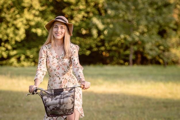 Junge, dünne, blonde frau auf fahrrad gegen defocused parklandschaft. herbstfarbton.