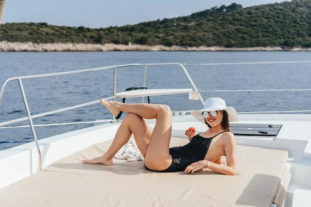 Junge dünne frau, die im bikinibadeanzug auf einer yacht in der sonnenbrille sitzt und in der sonne sich aalt