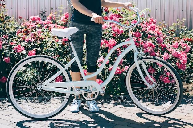 Junge dünne frau, die mit fahrrad auf einem hintergrund von büschen mit rosen steht