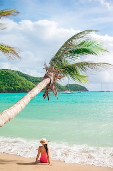 Junge dünne frau im bikini und in strohhut, die auf tropischem strand liegen. schönes mädchen unter der palme im seichten wasser