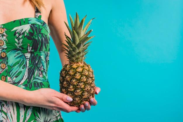 Junge dünne frau im geblühten kleid, das ananas hält