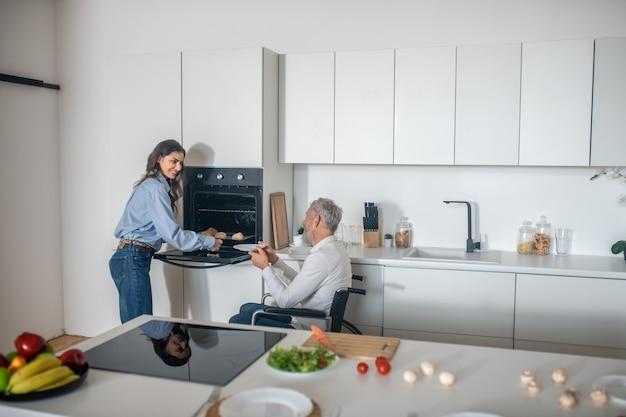 Junge dunkelhaarige frau bereitet frühstück für ihren behinderten ehemann zu