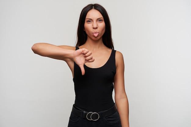Junge dunkelhaarige frau mit lässiger frisur, die hand in abneigungsgeste anhebt, während sie posiert, sich verzieht und zunge zeigt