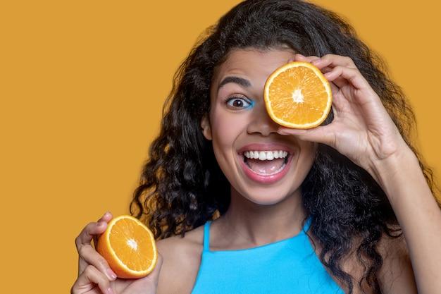 Junge dunkelhaarige frau mit orange in den händen
