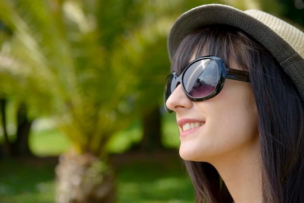 Junge dunkelhaarige frau mit sonnenbrille im park