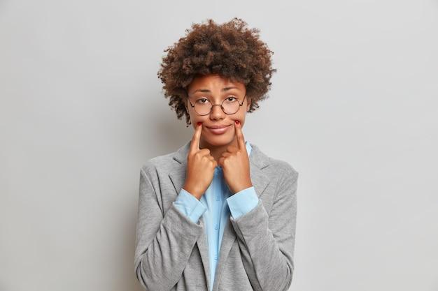 Junge dunkelhäutige frau mit afro-haar hält finger in der nähe von lippen ecken zwingt fröhliches lächeln