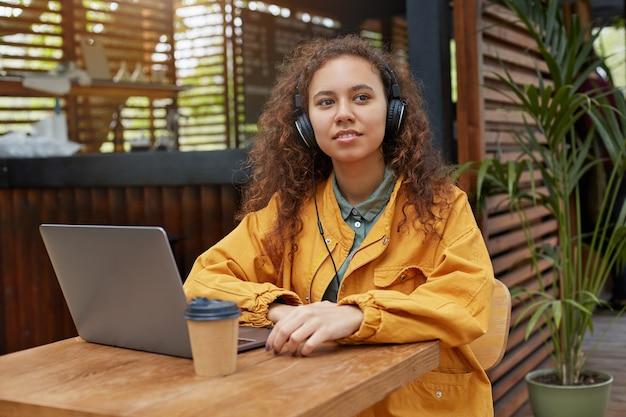 Junge dunkelhäutige lockige studentin sitzt auf einer caféterrasse und schaut weg, trägt einen gelben mantel, trinkt kaffee, arbeitet an einem laptop und hört musik.