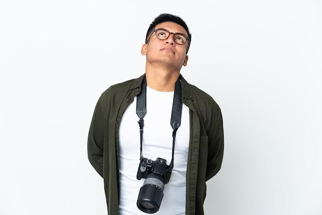 Junge ecuadorianische fotografin isoliert auf weißem hintergrund und nach oben schauend