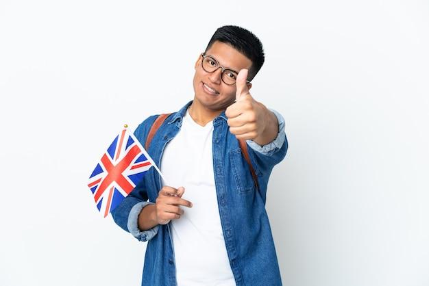 Junge ecuadorianische frau, die eine britische flagge hält, die auf weißer wand mit daumen oben isoliert wird, weil etwas gutes passiert ist