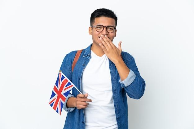 Junge ecuadorianische frau, die eine britische flagge lokalisiert auf weißem hintergrund glücklich und lächelnd bedeckt mund mit hand hält