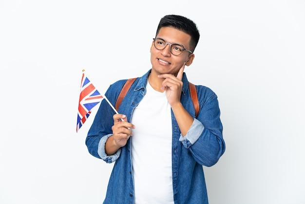 Junge ecuadorianische frau, die eine britische flagge lokalisiert auf weißer wand hält, die eine idee beim nachschlagen denkt