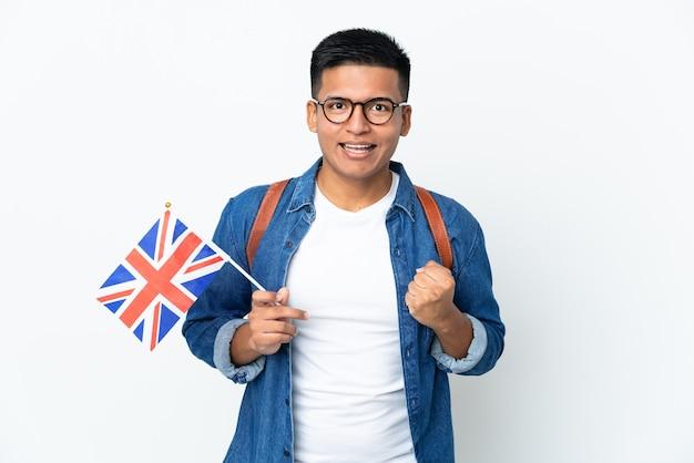 Junge ecuadorianische frau, die eine britische flagge lokalisiert auf weißer wand hält, die einen sieg in der siegerposition feiert