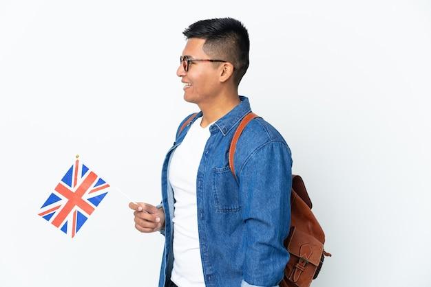Junge ecuadorianische frau, die eine britische flagge lokalisiert auf weißer wand hält, die in seitlicher position lacht