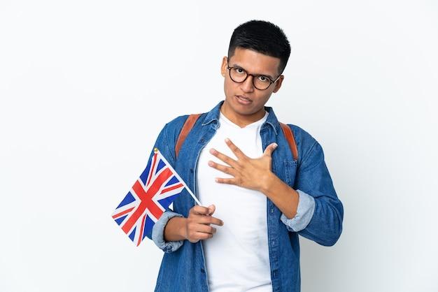 Junge ecuadorianische frau, die eine britische flagge lokalisiert auf weißer wand hält, überrascht und schockiert, während sie nach rechts schaut