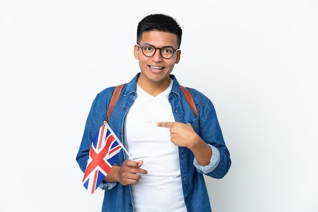 Junge ecuadorianische frau, die eine britische flagge lokalisiert auf weißer wand mit überraschendem gesichtsausdruck hält Premium Fotos