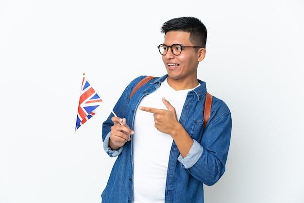 Junge ecuadorianische frau, die eine flagge des vereinigten königreichs lokalisiert auf weißem hintergrund zeigt, zeigt finger zur seite und präsentiert ein produkt