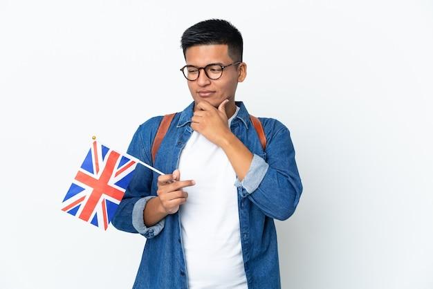 Junge ecuadorianische frau, die eine flagge des vereinigten königreichs lokalisiert auf weißer wand hält, die zur seite schaut und lächelt