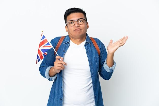 Junge ecuadorianische frau, die eine flagge des vereinigten königreichs lokalisiert auf weißer wand hält, die zweifel beim erhöhen der hände hat