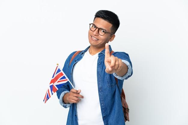 Junge ecuadorianische frau, die eine flagge des vereinigten königreichs lokalisiert auf weißer wand zeigt, die einen finger zeigt und anhebt