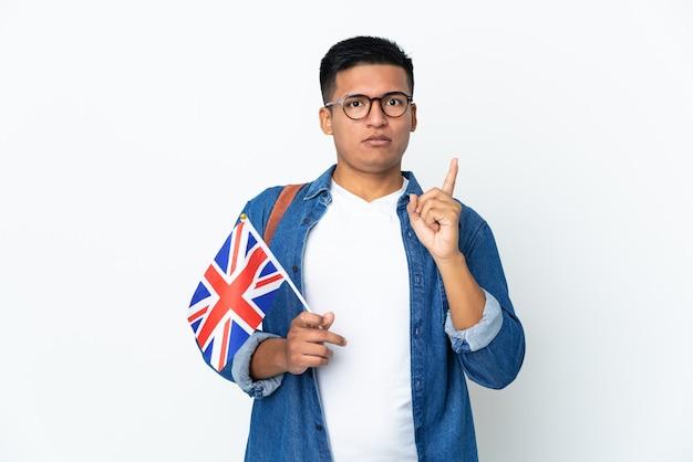 Junge ecuadorianische frau, die eine großbritannienflagge lokalisiert auf weißem hintergrund hält, die beabsichtigt, die lösung zu realisieren, während ein finger anhebt
