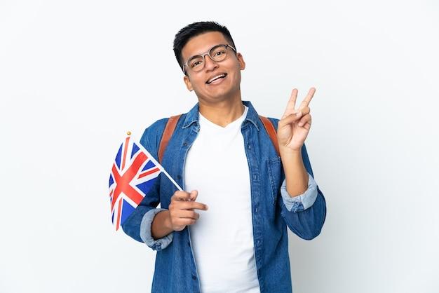 Junge ecuadorianische frau, die eine großbritannienflagge lokalisiert auf weißem wandlächeln und siegeszeichen zeigt hält