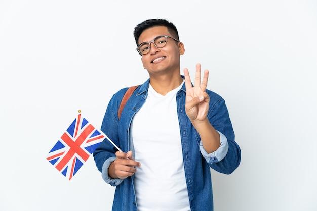 Junge ecuadorianische frau, die eine großbritannienflagge lokalisiert auf weißer wand glücklich hält und drei mit den fingern zählt