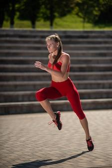 Junge eignungsfrau, die am stadion läuft. das konzept eines gesunden lebensstils