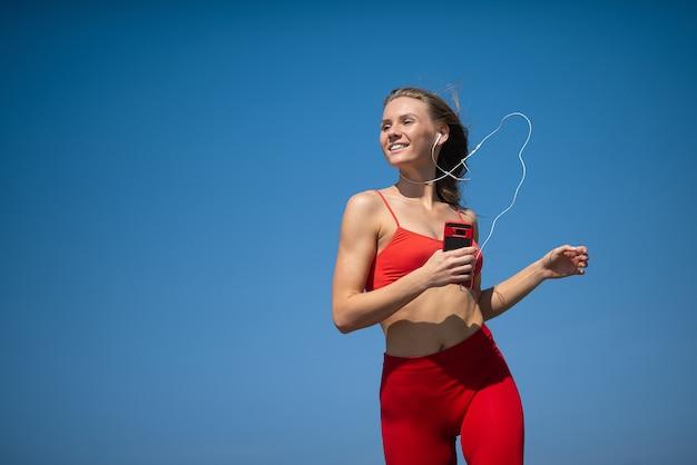 Junge eignungsfrau, die auf himmel backround läuft. das konzept eines gesunden lebensstils