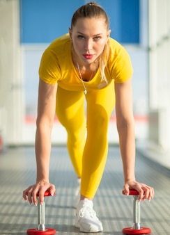 Junge eignungsfrau, die mit dummkopf in der turnhalle, sportkonzept ausarbeitet