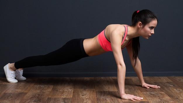 Junge eignungsfrau, die plankenübung tut