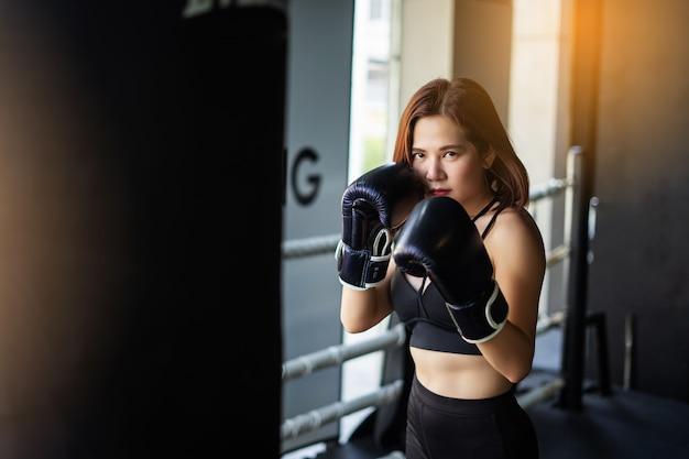 Junge eignungsfrau führen übung mit übung durch. fitness-sporthalle. frauen boxen.