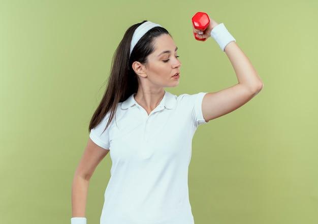 Junge eignungsfrau im stirnband, die mit der hantel anhebenden hand arbeitet, die bizeps zeigt, der zuversichtlich steht über heller wand steht