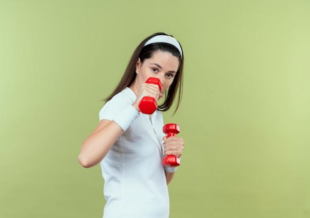 Junge eignungsfrau im stirnband, die mit hanteln arbeitet, die kamera mit dem sicheren ausdruck betrachten, der über hellem hintergrund steht