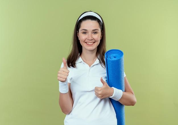 Junge eignungsfrau im stirnband, die yogamatte betrachtet, die kamera glücklich und positiv lächelnd zeigt, die daumen oben stehen über hellem hintergrund
