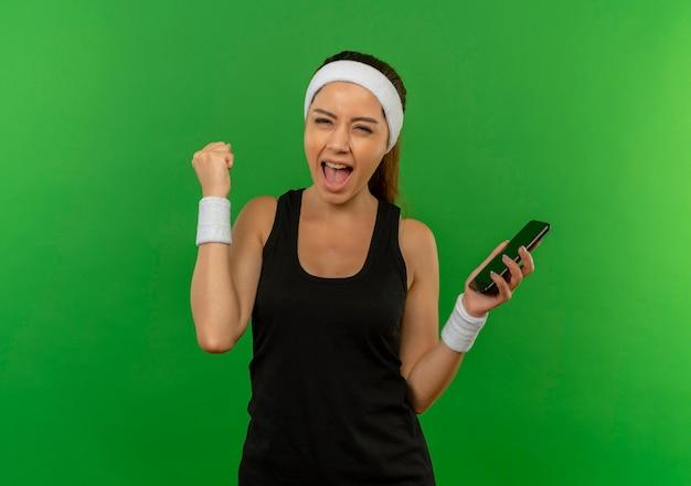 Junge eignungsfrau in der sportbekleidung mit dem stirnband, das smartphone hält, das faust glücklich und aufgeregt über grüner wand steht