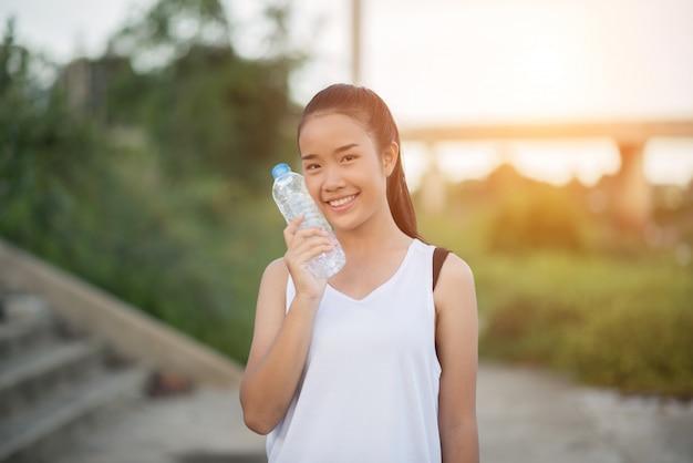 Junge eignungsfrauenhand, die wasserflasche hält, nachdem übung laufen gelassen worden ist