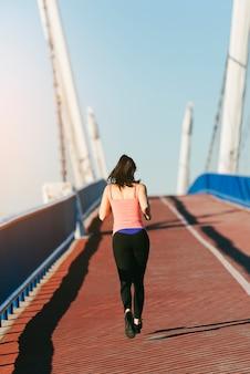 Junge eignungsfrauenläufer, der auf stadtbrücke läuft. sport-konzept.