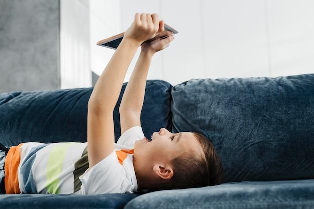 Junge ein haus, das auf der couch liegt und digitales tablett benutzt
